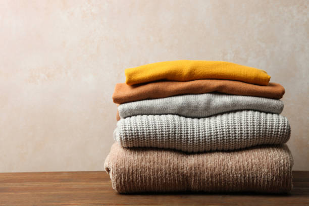 autumn clothes Pile of female warm sweaters on wooden table on neutral background. Concept autumn clothes. sweater stock pictures, royalty-free photos & images