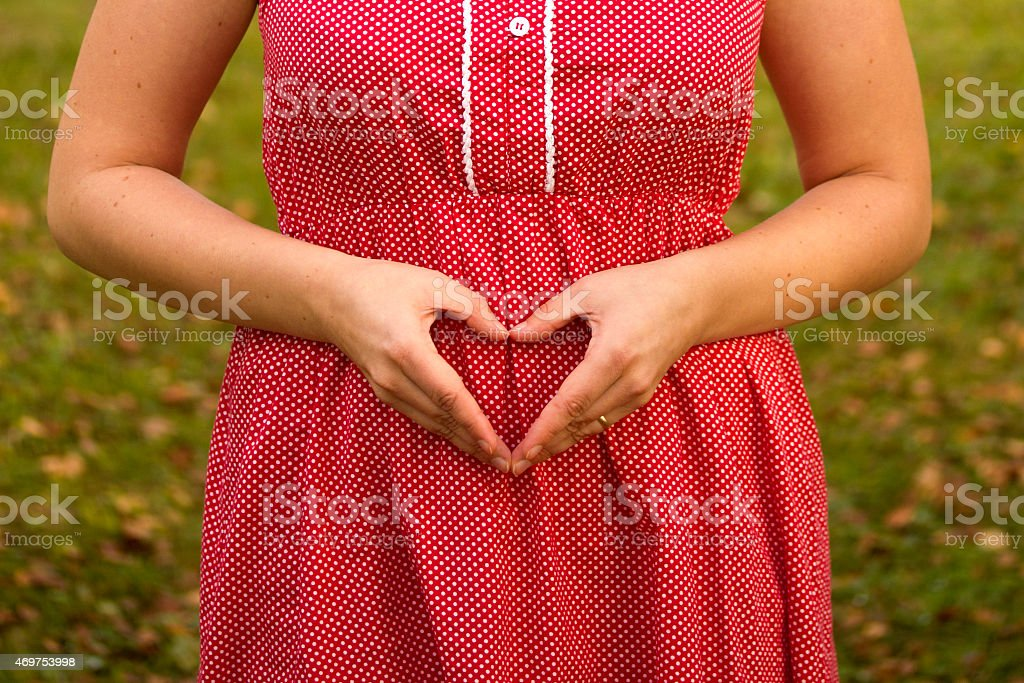 Autumn colored image of woman's hands forming heart over belly stock photo