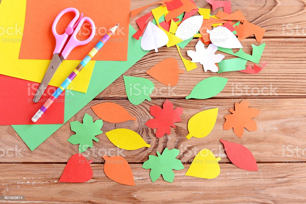 Autumn colored paper leaves on wooden background stock photo