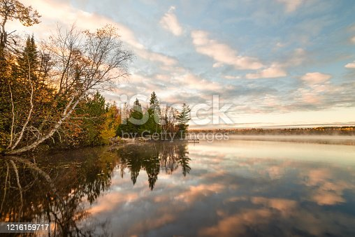 Fall colored trees on water's edge clouds reflection in Minnesota lake.