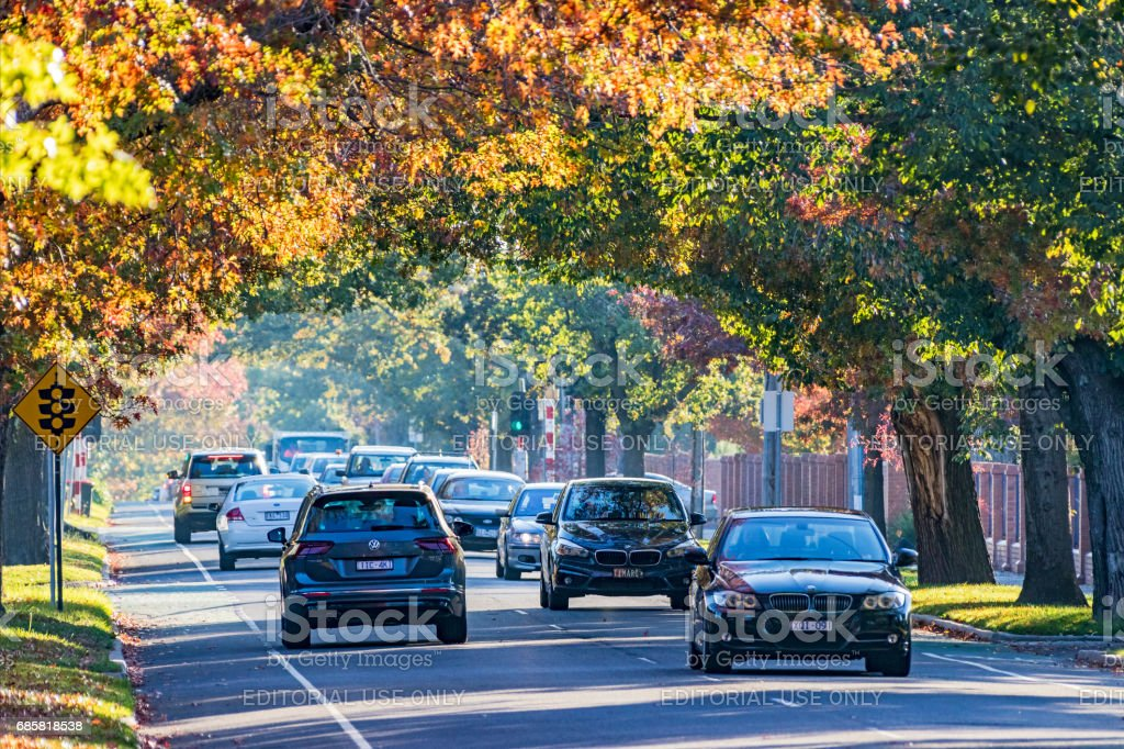 Autumn colors on busy suburban road, traffic in both directions stock photo