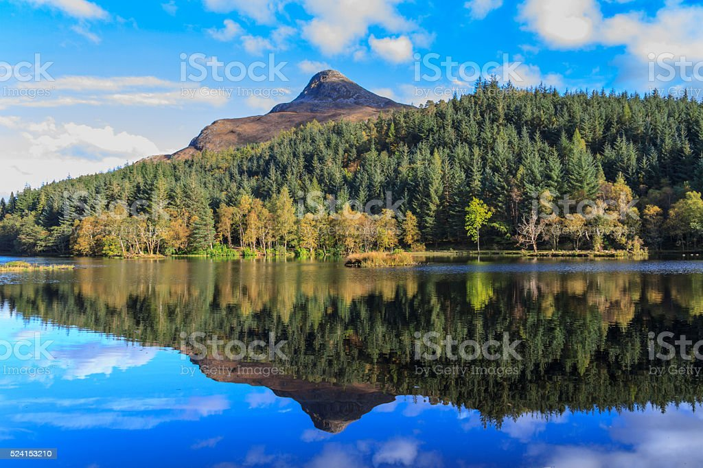 Autumn colour & pyramid-shape mountain reflected in lake stock photo