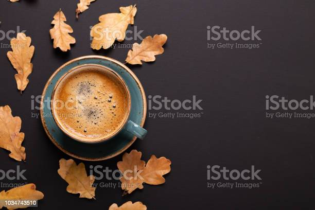Photo of Autumn composition. Cup of coffee and dry leaves on black background.