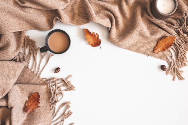 Autumn composition. Cup of coffee, plaid, autumn leaves on white background. Flat lay, top view, copy space stock photo