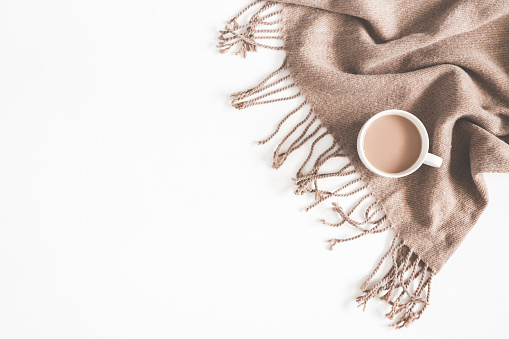 Autumn composition. Cup of coffee, plaid on white background. Autumn, fall concept. Flat lay, top view, copy space