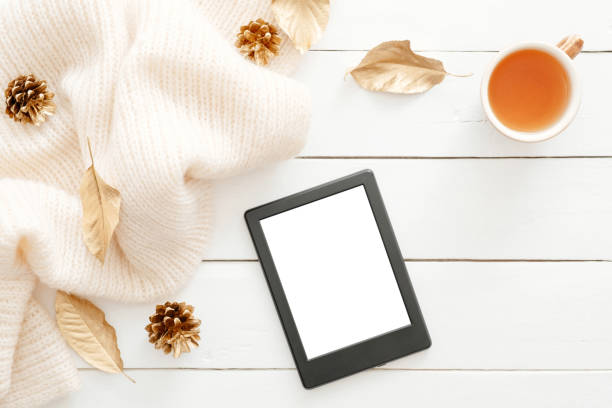 Autumn composition. Feminine desk table with knitted scarf, tea cup, cones, tablet ebook with blank screen, fall leaves on wooden background. Flat lay, top view. Nordic, hygge, cozy home concept