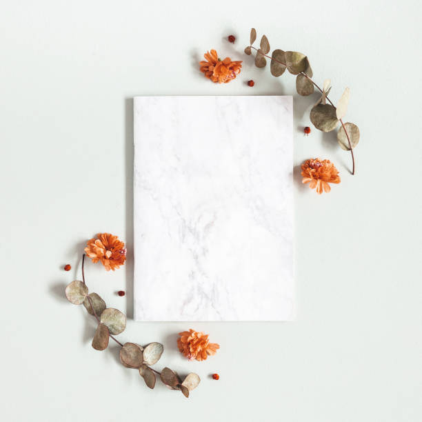Autumn composition. Paper blank, flowers, leaves on gray background. Autumn, fall, thanksgiving day concept. Flat lay, top view, copy space, square stock photo