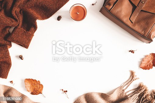 Autumn composition. Sweater, plaid, autumn leaves on white background. Flat lay, top view, copy space