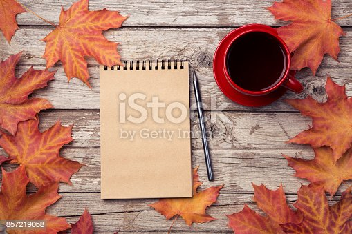 Autumn composition with workspace with blank notebook, pencil, red cup of coffee and beautiful red maple leaves. Top view, flat lay, vintage toning. Autumn relax concept