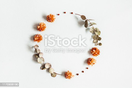 istock Autumn composition. Wreath made of dried flowers, eucalyptus leaves, berries on gray background. Autumn, fall, thanksgiving day concept. Flat lay, top view, copy space 1170938190
