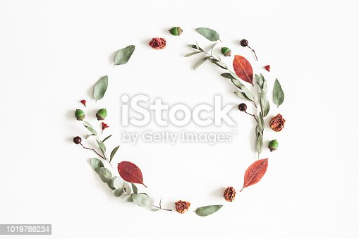 istock Autumn composition. Wreath made of eucalyptus branches, rose flowers, dried leaves on white background. Autumn, fall concept. Flat lay, top view, copy space 1019786234