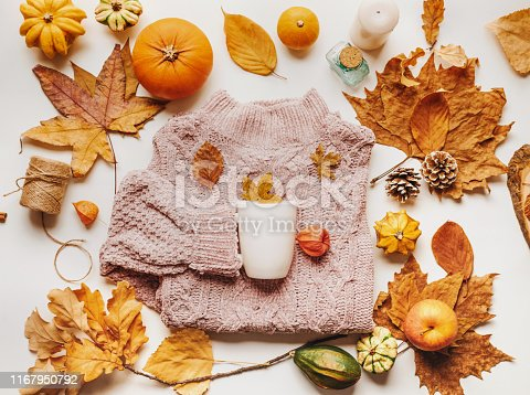 Autumn flat lay composition: sweater, cup, dry leaves and mini pumpkins