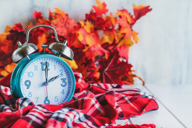 Autumn Daylight Savings Time Concept Daylight savings time concept. Set your clocks back with this retro beautiful alarm clocks set to 2 am over rustic white background with red plaid scarf and autumn leaves. Free space for text. daylight savings stock pictures, royalty-free photos & images