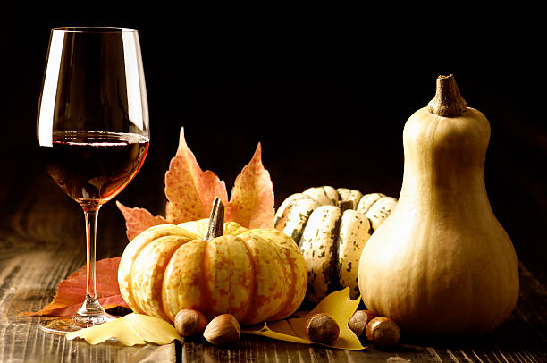 Autumn decor including pumpkins, gourds, wine and leaves stock photo