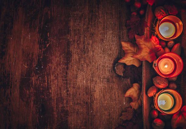 herbst dekoration-hintergrund mit kerzen, kürbisse, blätter und nüssen - herbst kerzen stock-fotos und bilder