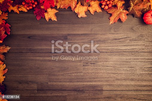 Autumn decoration with leafs and other season material on wooden background.
