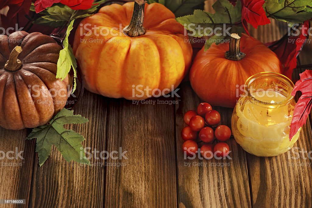 Autumn decoration with candle, maple leaves and pumpkins royalty-free stock photo
