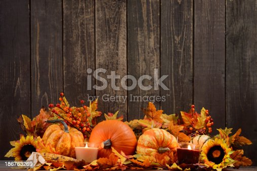 istock Autumn decoration with maple leaves and pumpkins on old woods 186763269