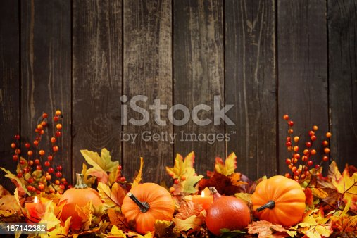 istock Autumn decoration with maple leaves and pumpkins on old woods 187142362