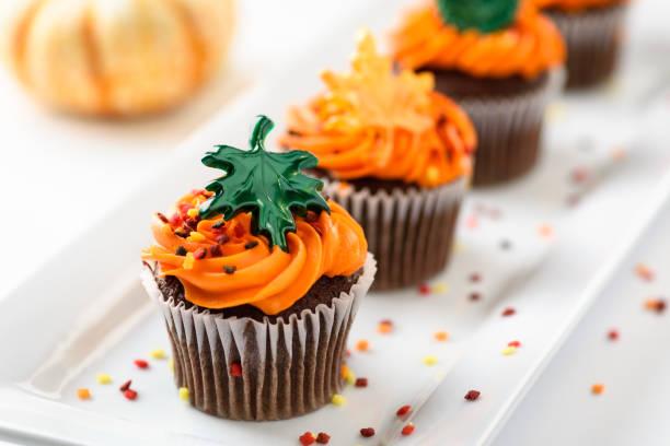 im herbst leckere muffins verziert mit orange zuckerguss, bunten streuseln und ahorn blätter - cupcake, zuckerguss stock-fotos und bilder