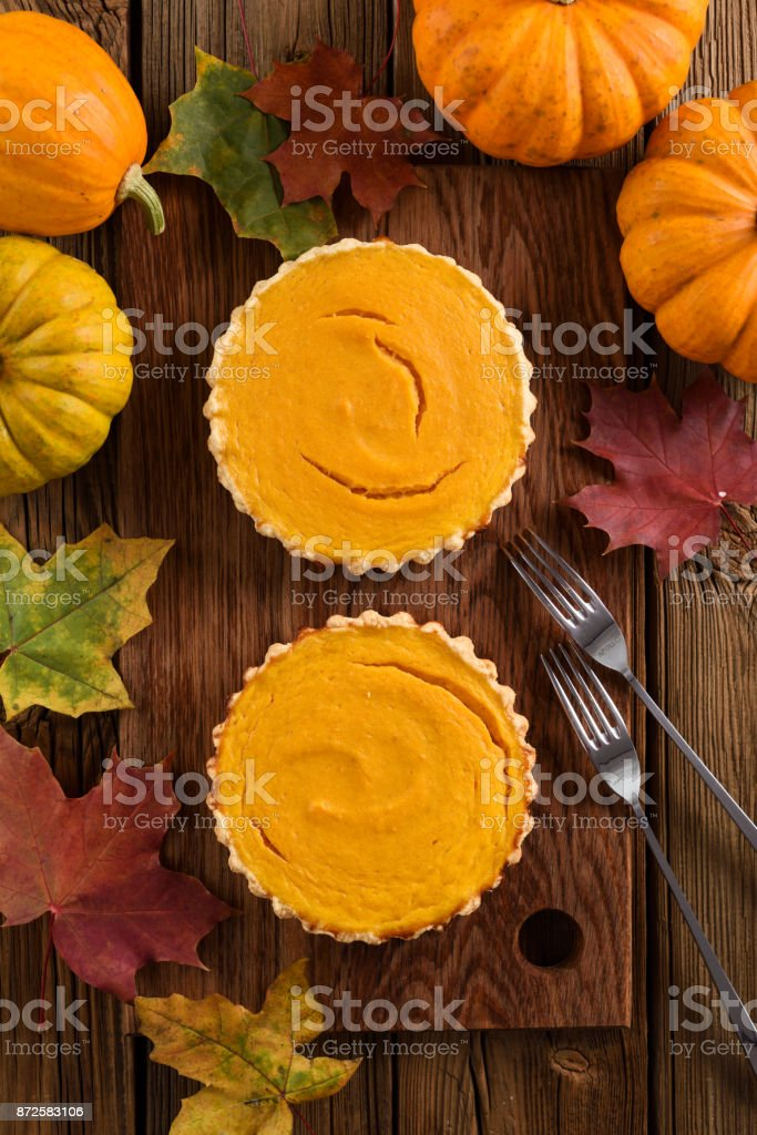 Autumn dessert flatlay. Couple of small simple pumpkin pies decorated with bright orange pumpkins and marple leaves stock photo