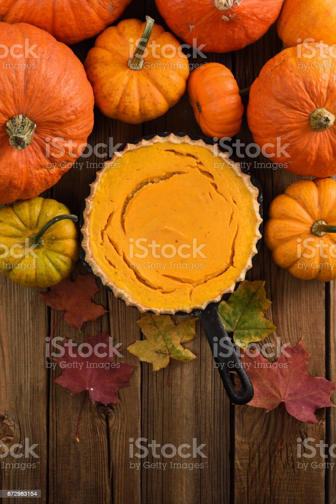 Autumn dessert. Open pumpkin pie decorated with bright orange pumpkins and marple leaves on rustic wooden background copy space stock photo