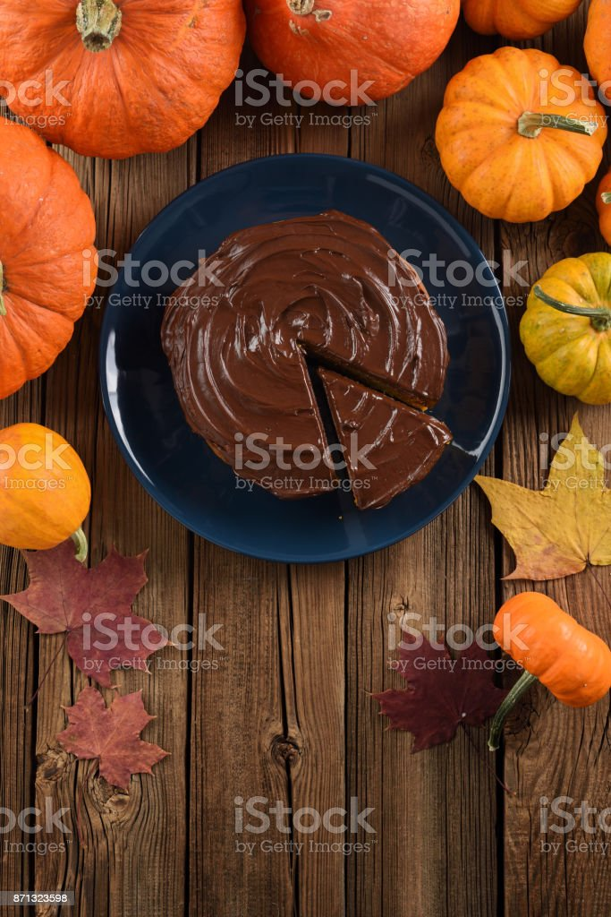Autumn dessert. Tasty chocolate cake served with bright orange pumpkins and marple leaves on old wooden background copy space stock photo
