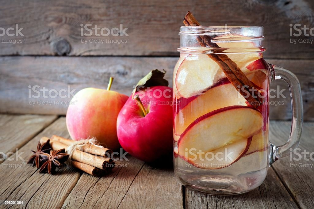 Autumn detox water in a mason jar on rustic wood stock photo