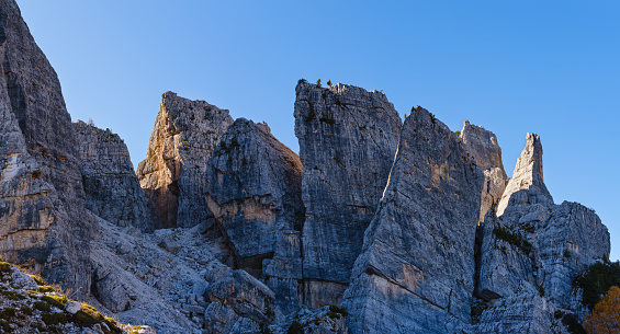 Sunny autumn alpine Dolomites rocky  mountain scene, Sudtirol, Italy. Cinque Torri (Five pillars or towers) rock famous formation. Picturesque traveling, seasonal, hiking, nature beauty concept scene. Climbers unrecognizable.