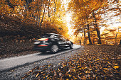 Motion blurred car on a country road through the colorful autumn forest. Low angle view.
