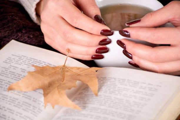 herbst welkes blatt auf buch und mädchen die hände mit braunen maniküre nägel finger hält tasse tee - herbst nagellack stock-fotos und bilder