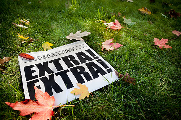 Autumn EXTRA! Newspaper on Grass with Fall Leaves Color photo of a daily newspaper announcing