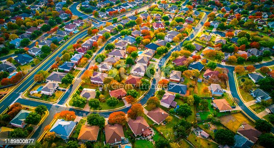 Autumn fall colors high above Suburb modern housing development in Austin Texas USA aerial drone view high above Suburb community neighborhood houses and homes rooftop and buildings. Real estate industry expanding into Round Rock , Cedar Park , and surrounding central texas