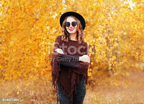 469211680 istock photo Autumn fashion portrait pretty smiling woman wearing black hat poncho 614027464
