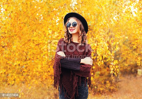 469211680 istock photo Autumn fashion portrait smiling woman wearing black hat poncho 614027404