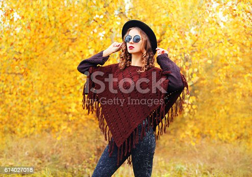 469211680 istock photo Autumn fashion young woman model wearing black hat sunglasses poncho 614027018