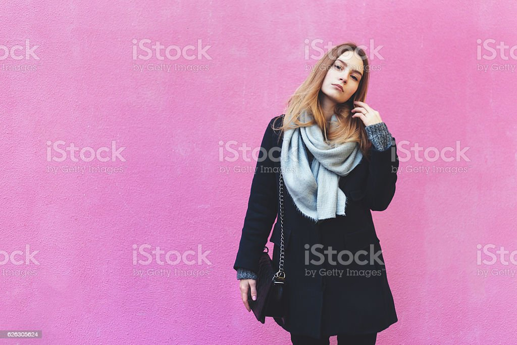Autumn fashion young woman posing near pink wall stock photo