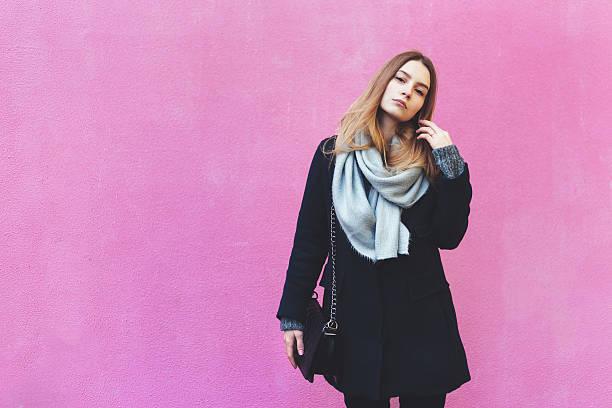 Autumn fashion young woman posing near pink wall stock photo