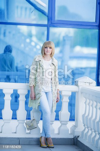 469211680 istock photo Autumn fashionable image of cute young woman with short hairs and candid smile. Trendy coat, denim jeans. Student female posing inver yellow wall. Outdoor . 1131152423