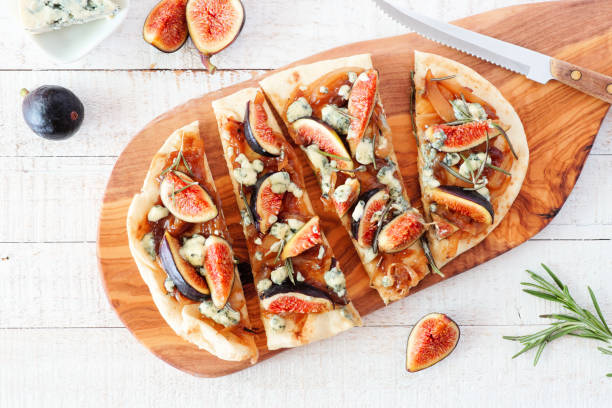 Autumn flat bread pizza with figs, caramelized onions, blue cheese and rosemary, top view table scene on white wood stock photo