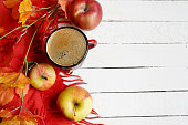 autumn flatlay background with cup of coffee, yellow leaves and and red apples on white wooden table, copy space