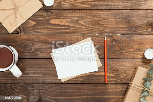 Autumn flatlay composition with letter, blank paper card, cup of tea, gift box, envelope, candles on wooden background. Cozy autumn or winter holiday concept. Flat lay, top view