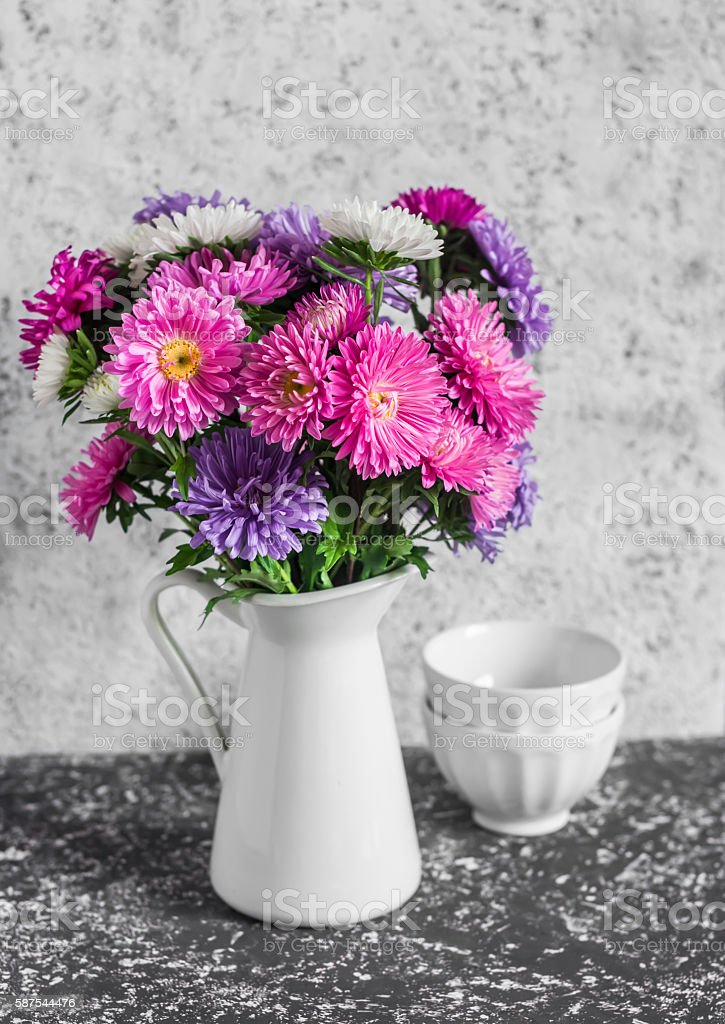 Autumn flowers asters in a white pitcher. Vintage style stock photo