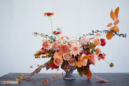 Beautiful flower composition with autumn orange and red flowers and berries. Autumn bouquet in vintage vase on a white wall background