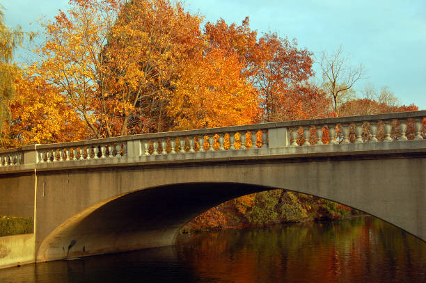 Autumn foliage surrounds a stone bridge spanning a lake stock photo