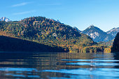 Autumn forest by the lake and snow on top of the Alps in morning sun
