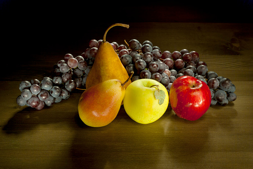 pears, apples and grapes on wooden table background