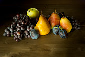 pears, apples, grapes and plums on wooden table