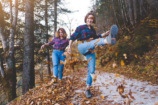istock autumn fun. Two happy girls in the forest throw dry leaves
