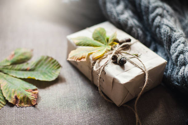 Autumn gifts with fallen leaves. Present for Thanksgiving day is wrapped in kraft paper in rustic style. stock photo
